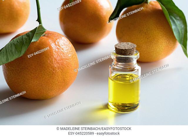 A transparent bottle of tangerine essential oil with fresh tangerines on white background