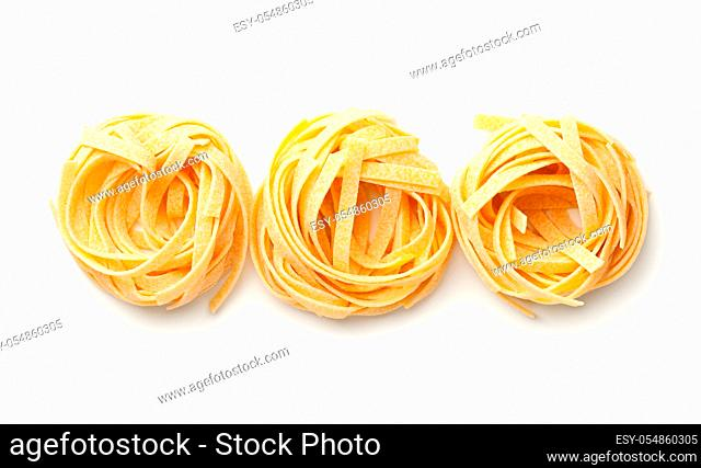 Raw tagliatelle pasta nests isolated on white background. Top view