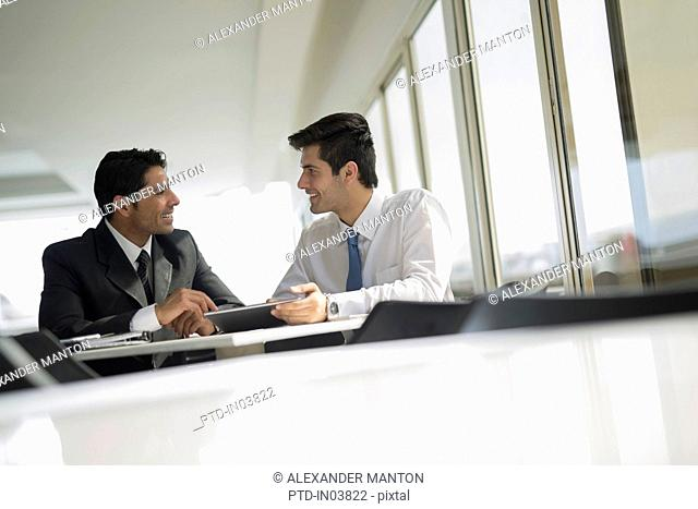 India, Two male colleagues working in cafeteria