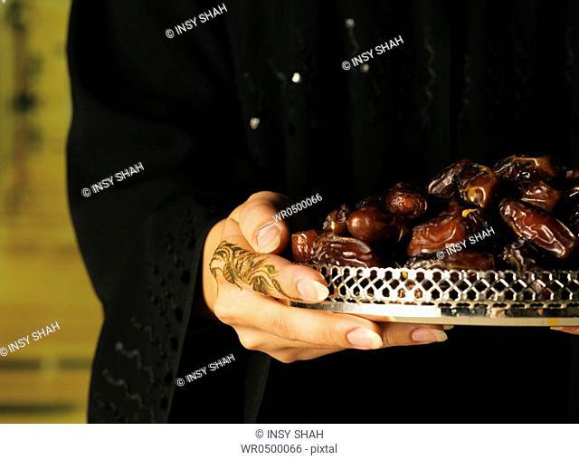 Arab women henna on hands holding dates