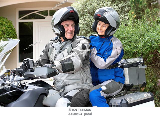 Happy senior couple wearing helmets on motorcycle in driveway