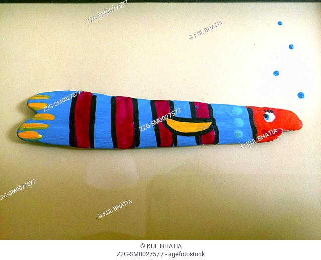 A fish with eyelashes painted in bold colours on driftwood, bubbles blowing on the background paper, a playful scene for a child's nursrey, Halifax, Nova Scotia