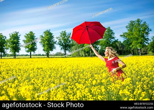 Happy woman holding red umbrella while standing amidst oilseed rapes