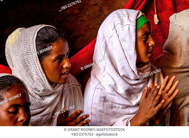 Young Female Pilgrims Singing and Clapping at Bete Abba Libanos Church, Lalibela, Ethiopia