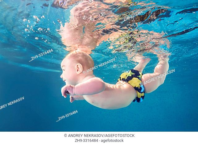 Little baby boy learning to swim underwater in a swimming pool. Healthy family lifestyle and children water sports activity