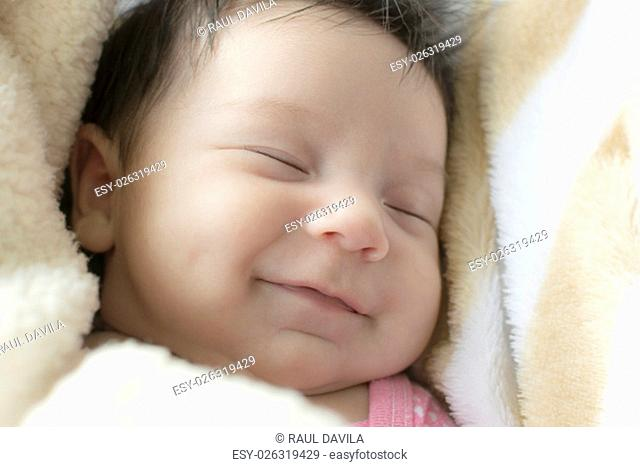 Little newborn girl with an expression of joy and a big smile while she sleeps