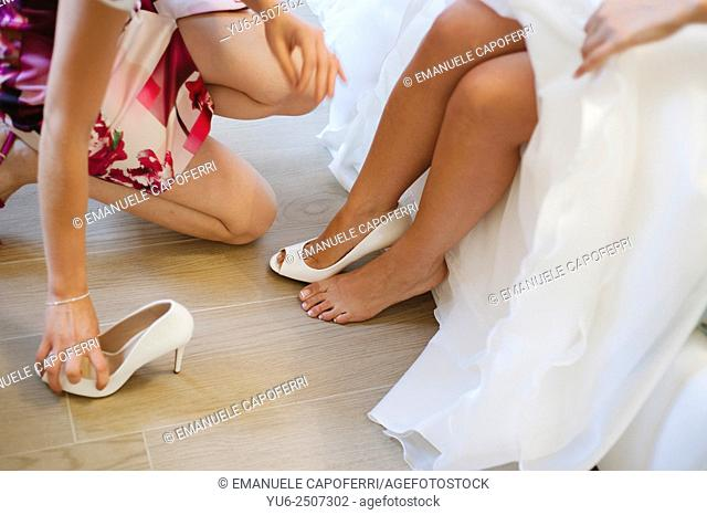 The bride puts shoes