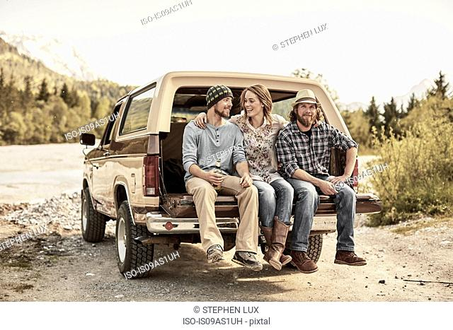 Three people sitting on back of pickup truck, arms around shoulders, smiling