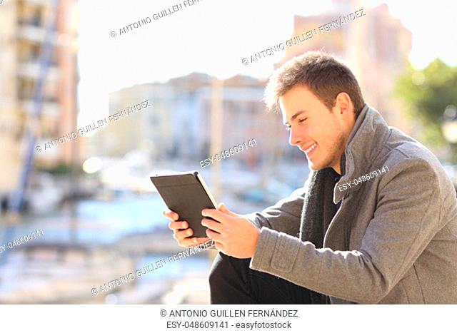 Side view portrait of a happy man uses a tablet outside in the street of a coast town