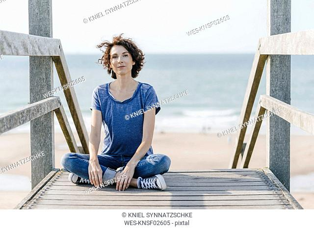 Portrait of woman sitting on boardwalk at the beach
