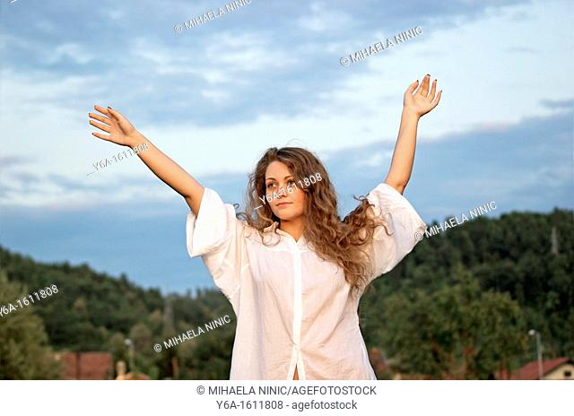 Portrait of a content young woman outdoors with arms raised