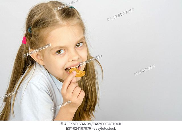 Portrait of a little six year old girl biting a cookie