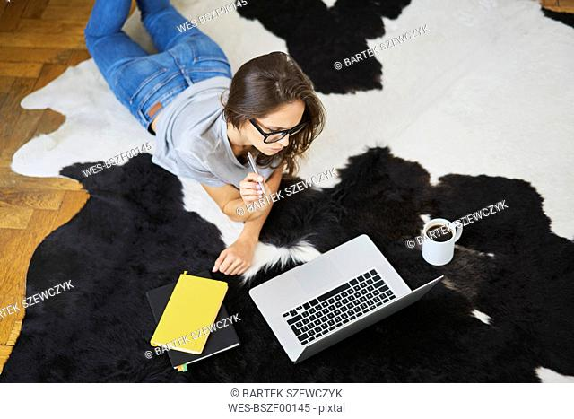 Young woman at home lying on the floor using laptop