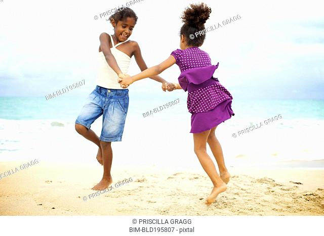 Mixed race sisters holding hands playing on beach