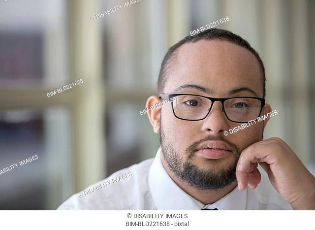 Mixed race man with down syndrome resting chin in hands