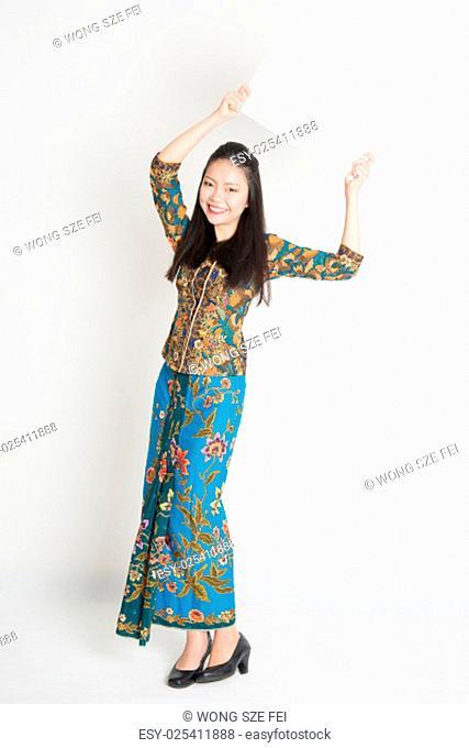 Full body portrait of Southeast Asian girl in batik dress hands holding white blank poster standing on plain background