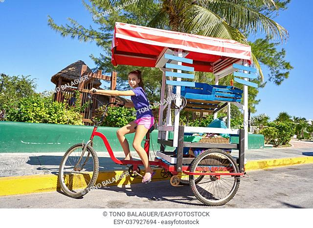 Young girl with caribbean bicycle shop on tricycle of Mexico