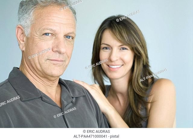 Man and woman smiling at camera, portrait