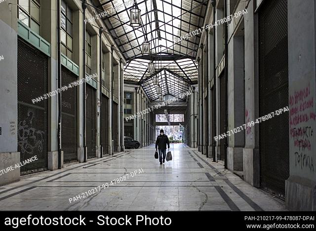 17 February 2021, Greece, Athen: A man walks past closed shops in the centre of Athens. A strict lockdown has been in effect for the greater Athens area for a...