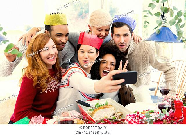 Friends wearing paper crowns taking selfie at Christmas dinner