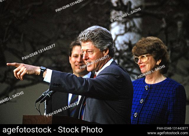 United States President Bill Clinton, center, answers a reporter's question after introducing Janet Reno, State's Attorney for Miami-Dade County, Florida, right