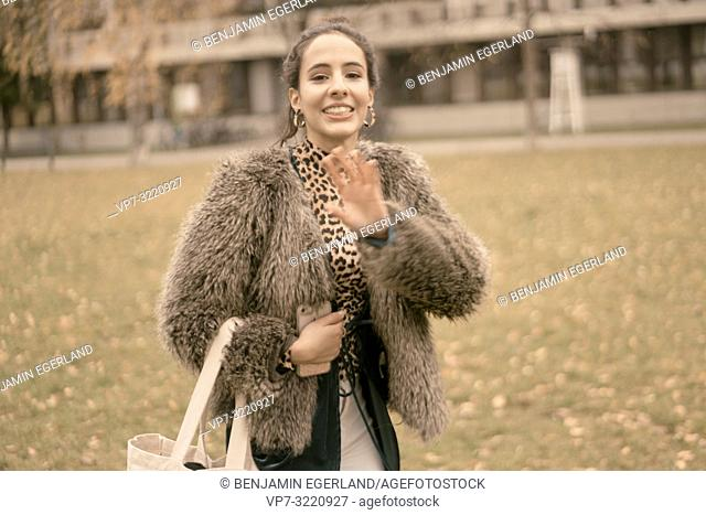 fashionable lively woman waving hands, gesticulating while walking outdoors in park, autumn season, wearing coat, happy, candid emotion, unposed walking in city
