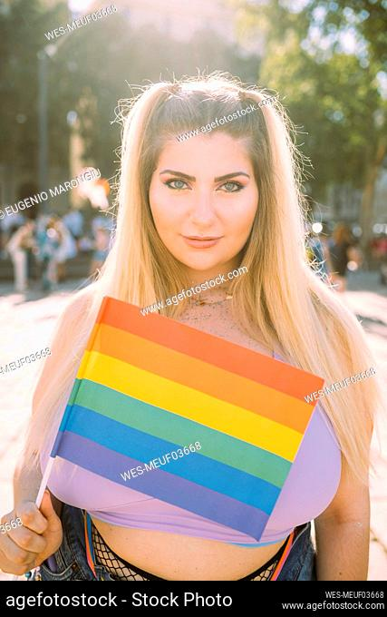 Young woman with rainbow flag during sunny day