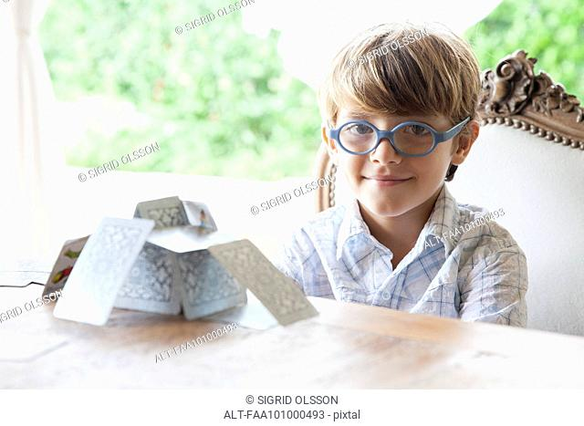 Little boy building house of cards