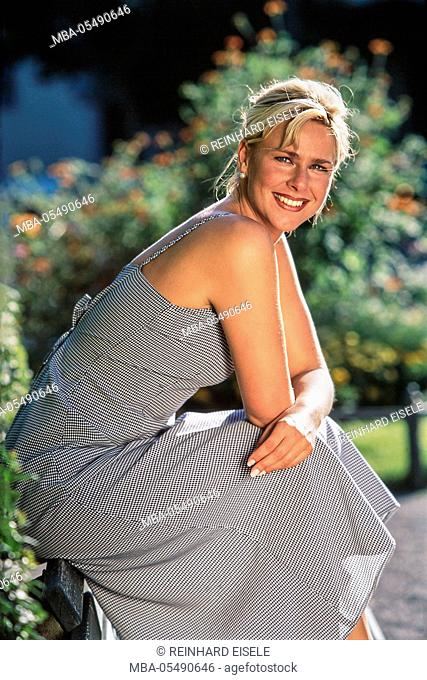 Smiling young blond woman sits on the armrest of a bank