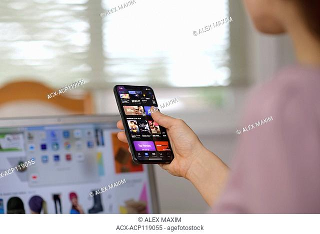 Woman browsing through iTunes store movie list on Apple iPhone X. Closeup of her hand holding an iPhone with indoor home settings in the background