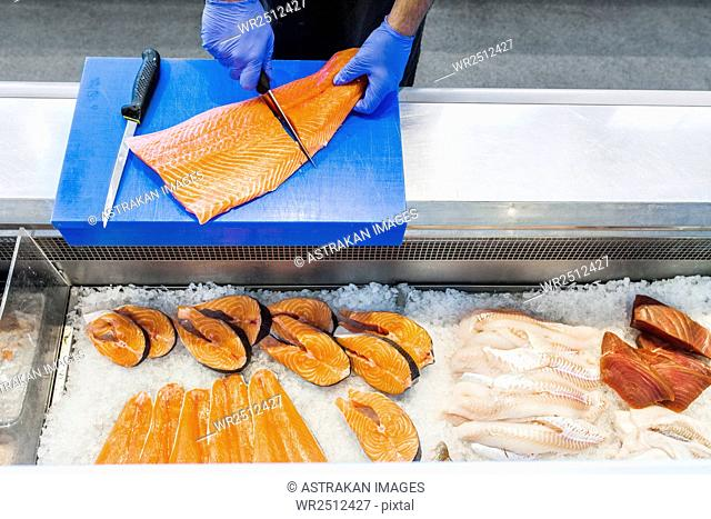 Cropped image of fish vendor cutting salmon at refrigerated section in supermarket