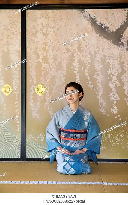 Young Japanese woman in kimono sitting in front of Fusuma (Japanese traditional partition from paper)