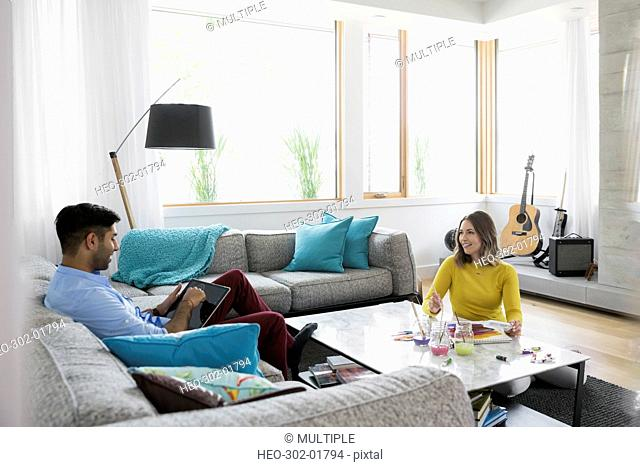Young couple relaxing and painting with watercolors in living room