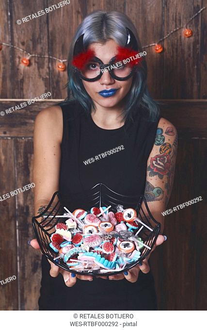 Masqueraded young woman offering Halloween candies