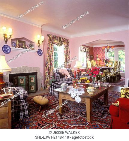 LIVING ROOM - to the fireplace. Antique pine coffee table, lace doily ,heavy floral swag drapes, buffalo check fabric chairs and ottoman, pink walls