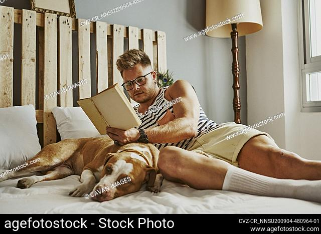 A young blond boy reading in bed with his dog