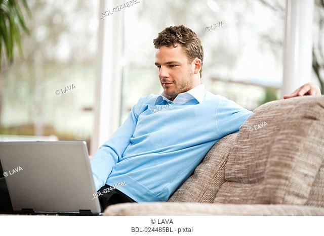 portrait of young man working with laptop computer at home