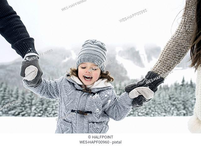 Happy girl hand in hand with parents in winter landscape