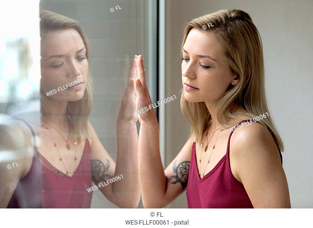 Portrait of blond young woman and her reflection on windowpane