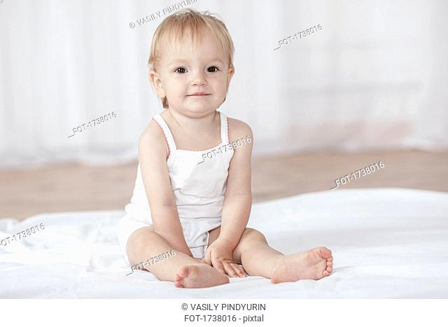 Portrait of cute baby girl sitting on bed at home