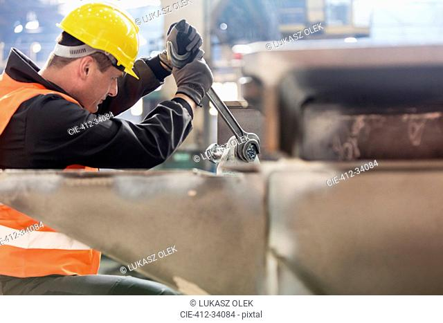 Steel worker using large wrench in factory