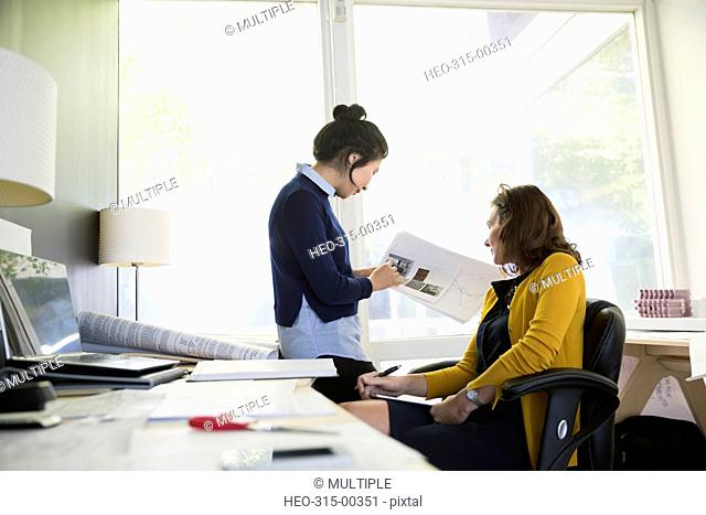 Female architects meeting and discussing blueprints in office