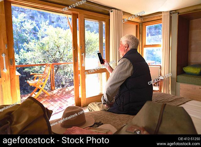 Senior man using smart phone on hotel bed