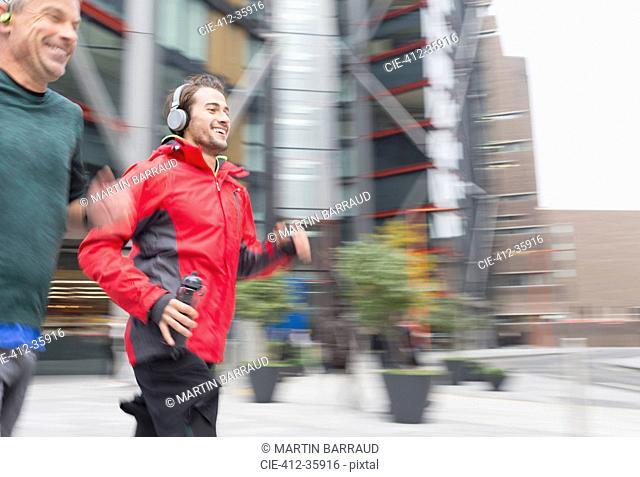 Smiling men running, wearing headphones on urban sidewalk