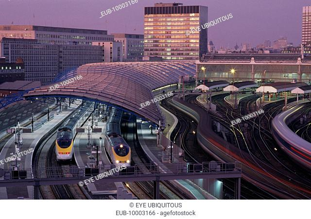 Waterloo Station International Terminal with Eurostar trains in evening. City buildings behind
