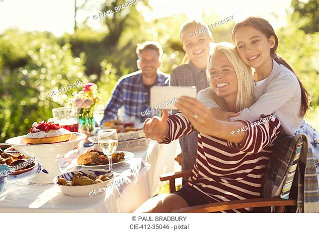 Mother and daughters taking selfie with camera phone at garden party patio table