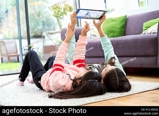 Girls taking selfie with digital tablet on living room floor