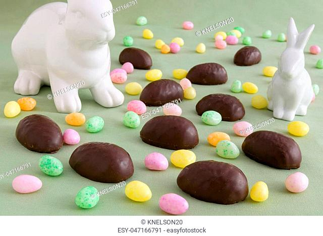 Two white ceramic Easter bunnies in a field of chocolate covered marshmallow eggs and colorful jelly beans