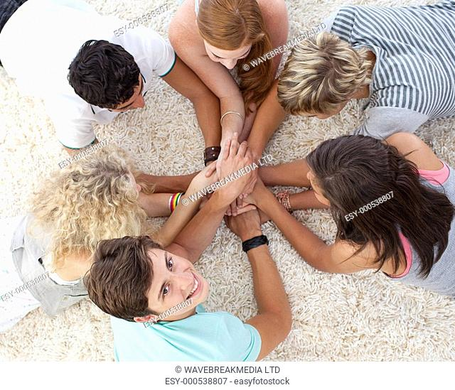 Group of teenagers lying on the floor with hands together