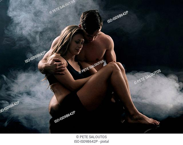 Man carrying woman against smoky background